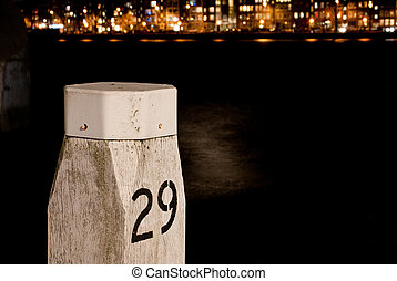Port pole with a night life cityview of rotterdam with...