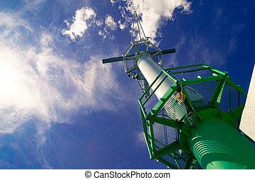 Port radar in the harbor against blue cloudy sky and sun rays
