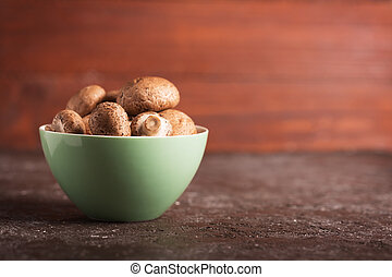 Portabello mushrooms in a green bowl on a dark background -...