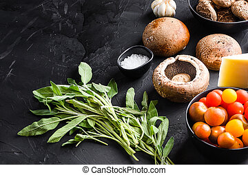 Portabello mushrooms ingredients for baking, cheddar cheese and sage on black background. Side view
