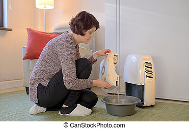 Portable dehumidifier colect water from air - Woman with...