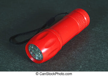 Portable LED flashlight red color isolate on a grey background. Close-up.