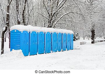 Portable plastic bio toilets - Snow covered blue street...