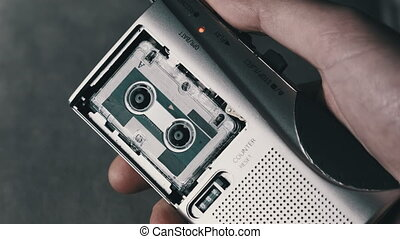 Portable Retro Cassette Recorder in Hand Push on Rec to Record Interviews. Rec of voice on a vintage handheld tape recorder. A player with Mini Cassette from 90s. Concept voice or call recording. 4K