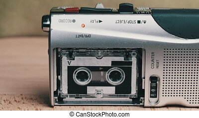 Portable vintage tape micro cassette recorder record sound on yellow background. Rec voice Interviews on a Mini Cassette on a handheld retro player. Close-up. Microcassette spins. 90s. Call recording.