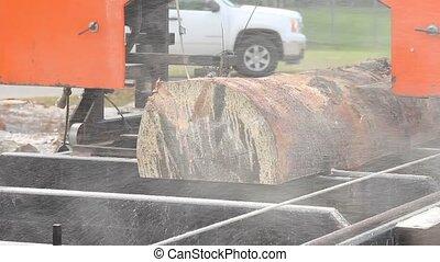 portable sawmill cutting a log into lumber