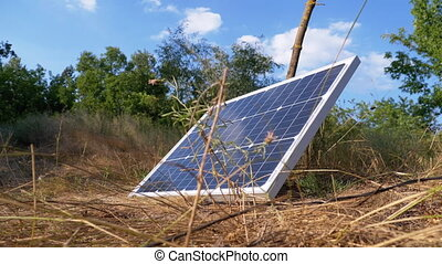Portable Solar Panel against a Blue Sky and Clouds Lying on the Ground in the Grass Used in Tourism. Solar energy in outdoor. Summer, sunny day. One big solar panel used for camping.