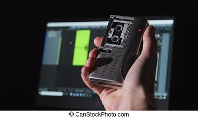 A portable cassette recorder in hand records sound. Recording of interviews on a mini tape retro recorder. A handheld voice recorder records a voice against the laptop with an audio recording spectrum