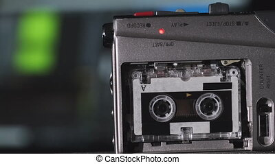 Portable Tape Recorder Records Sound or Interviews on a Mini Cassette. Rec of voice on a handheld voice vintage recorder. Records against laptop with an audio recording spectrum. Retro player 4K 10bit