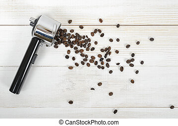 Portafilter handle with scattered coffee beans on wooden surface in top view