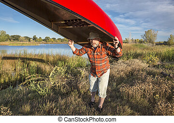 portaging canoe on a lake shore - senior male paddler is ...