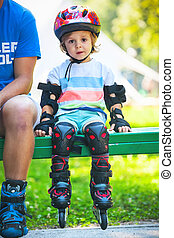 Portait of cute baby boy with  inline skates sitting on bench.
