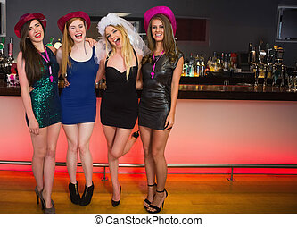 Portait of laughing friends having a hen party looking at...