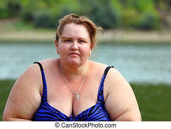 portarit of plump woman sitting near river