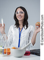 Portarit of Satisfied Female Laboratory Staff with Syringe and Apple Test Sample. Posing in Laboratory