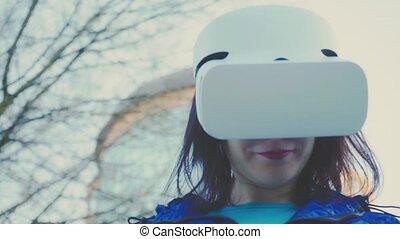 porter, bâtiment, femme, casque à écouteurs, vidéos, regarder, lunettes, jeune, virtuel, verre, vr, jeux, contre, fond, dehors, jouer