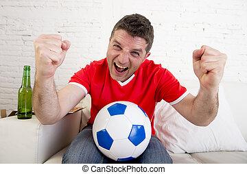 porter, but, regardant télé, sofa, football, célébrer, équipe, homme, jersey, heureux