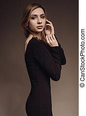 porter, femme, elle, long visage, toucher, robe noire, vue côté
