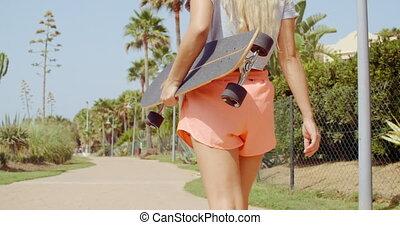 porter, femme, skateboard, vue postérieure