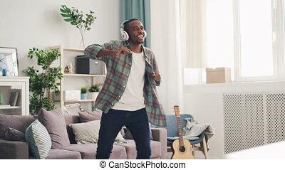 porter, flat., danse, shirt., chant, écouteurs, jean, américain, par, écoute, lumière, musique, type, homme, habillement, désinvolte, africaine, beau