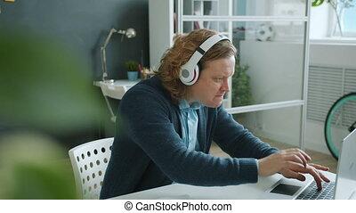 porter, heureux, musique, fonctionnement, dactylographie, alors, ordinateur portable, type, apprécier, danse, écouteurs, bureau