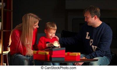 porter, mignon, avoir, famille, présente, room., heureux, garçon, ouverture, arbre, noël, gai, parents, joyeux, gifts., amusement, fetes, pyjamas, enfants, morning., aimer