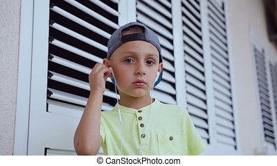 porter, mignon, bon garçon, habillé, casquette, isolé, chanson, t-shirt, arrière-plan., smartphone, musique écouter, portrait, blanc, gosse, écouteurs, écoute