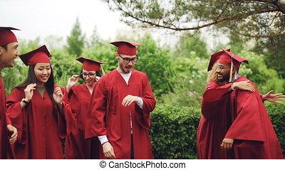 porter, traditionnel, hommes, gens, danse, garments., jeune, étreindre, jour, élevé, célébrer, rire, remise de diplomes, campus., cinq, femmes, excité, grads, dehors