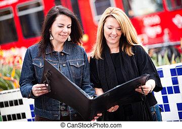 Portfolio - Businesswomen examine portfolio.