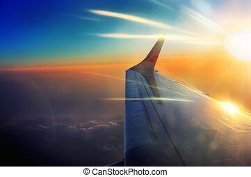 porthole view wing of the airplane in flight in sunrise beams