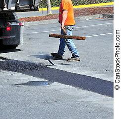 Portholes asphalt repairs by city crew outside.