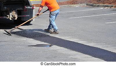 Portholes asphalt repairs by city crew.