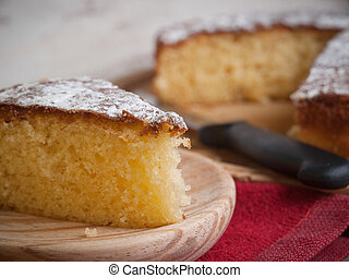 Portion of a sponge cake on a wooden plate in a studio shot.