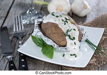 Portion of Baked Potato with Herbs on vintage wooden ...