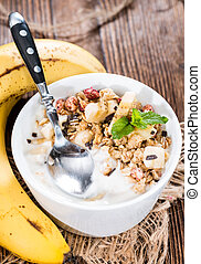 Portion of Banana Yogurt in a bowl with honey and muesli