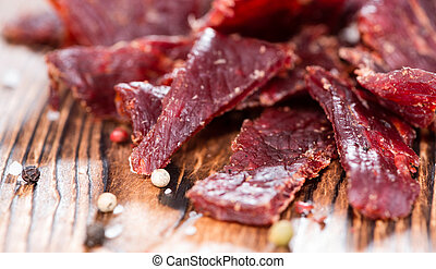 Beef Jerky - Portion of Beef Jerky on vintage wooden...