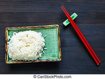portion of boiled rice on plate and red chopsticks