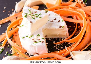 Portion of camembert cheese with carrot and healthy seeds