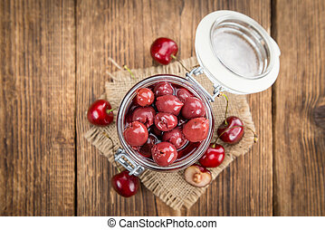 Portion of Canned Cherries on wooden background, selective ...