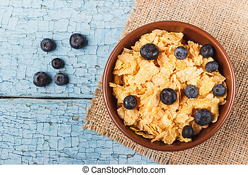 Portion of corn flakes in the bowl with blueberries