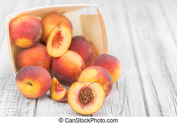 Portion of Fresh Peaches on wooden background, selective...