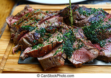Close up big portion of sliced grill roasted beef chateaubriand tenderloin meat with thyme and herbs served on wooden cutting board, high angle view