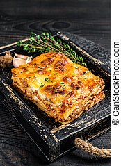 Portion of Lasagna with mince beef meat and tomato bolognese sauce in a wooden tray. Black wooden background. Top view