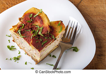 Portion of layered moussaka with parsley on plate