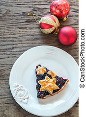 Portion of mince pie on the wooden background
