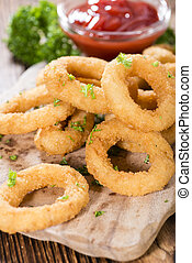 Portion of Onion Rings (homemade) with fresh herbs on an old...