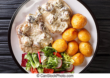 Portion of pork steak in a creamy mushroom sauce with a garnish of new potatoes and vegetable salad close-up. horizontal top view
