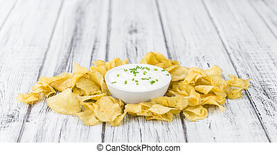 Portion of Potato Chips with Sour Cream taste on wooden...