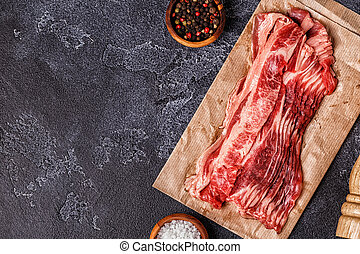 Portion of raw Bacon stripes on dark background.