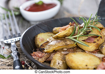Portion of roasted Potatoes with bacon and fresh herbs